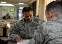 U.S. Air Force Tech Sgt. Eric Williams, 97th Medical Support Squadron NCO in charge of the base pharmacy, fills out a sheet to get a cold medication packs, April 10, 2017, at Altus Air Force Base, Oklahoma. The base pharmacy offers cold medication packs to those who meet their qualifications to help cut down on patient and health care provider's time and money. (U.S. Air Force Photo by Airman 1st Class Jackson N. Haddon/Released).