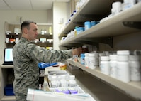 U.S. Air Force Capt. Michael Johnson, 97th Medical Support Squadron pharmacist, assembles a cold medication pack, April 10, 2017, at Altus Air Force Base, Oklahoma. The base pharmacy offers cold medication packs to those who meet their qualifications to help cut down on patient and health care provider's time and money. (U.S. Air Force Photo by Airman 1st Class Jackson N. Haddon/Released).