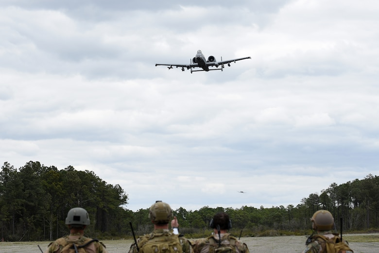 An A-10C Thunderbolt II flies over a group of tactical air control party specialists from the 14th Air Support Operations Squadron during exercise Razor Talon, April 7, 2017, at Atlantic Field Marine Corps Outlying Field, North Carolina. More than 10 aircraft from multiple bases participated in Razor Talon. (U.S. Air Force photo by Airman 1st Class Kenneth Boyton)