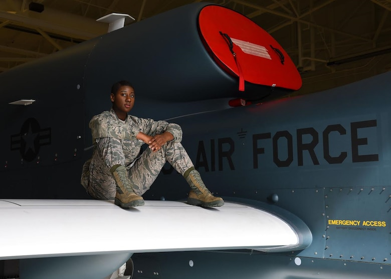 Airman 1st Class Celeste Black, a crew chief with the 69th Maintenance Group, demonstrates how strong the wings of the RQ-4 Global Hawk are by sitting on one at Grand Forks Air Force Base, N.D. March 28, 2017. Black said she has yet to deploy to work on the Global Hawk overseas because of her fight with cancer, but hopes to be able to soon. (U.S. Air Force photo by Airman 1st Class Elora J. McCutcheon