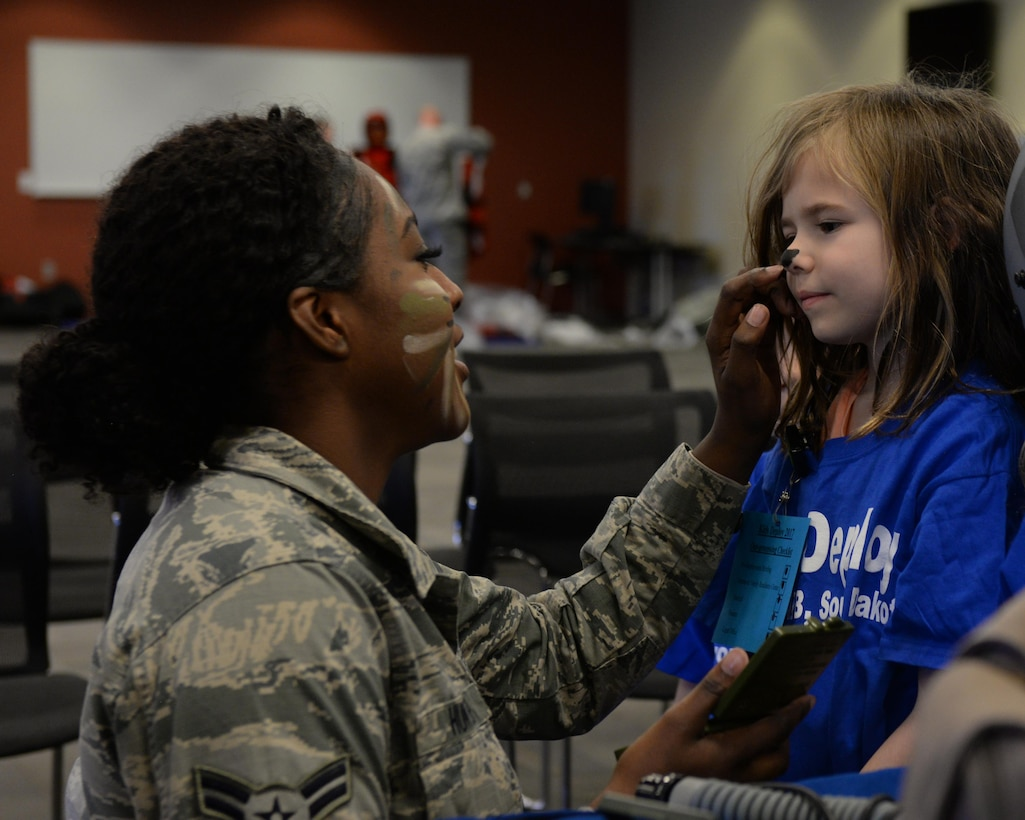 Airman 1st Class Deja Hunter, an aircrew flight equipment specialist assigned to the 28th Operations Support Squadron, paints the nose of a child going through the Kid's Deployment Line at Ellsworth Air Force Base, S.D., April 8, 2017. Airmen from the 28th OSS painted faces and brought flight equipment for children to try on and use. (U.S. Air Force photo by Airman Nicolas Z. Erwin)