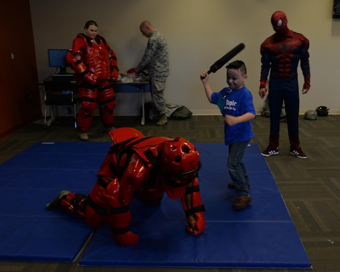 Airmen from the 28th Security Forces Squadron let children fight them with a foam baton during the Kid's Deployment Line at the deployment center on Ellsworth Air Force Base, S.D., April 8, 2017. The event was part of the Month of the Military Child, a Department of Defense initiative dedicated to recognizing and giving thanks to the children of U.S. military members for their courage and support. (U.S. Air Force photo by Airman Nicolas Z. Erwin)