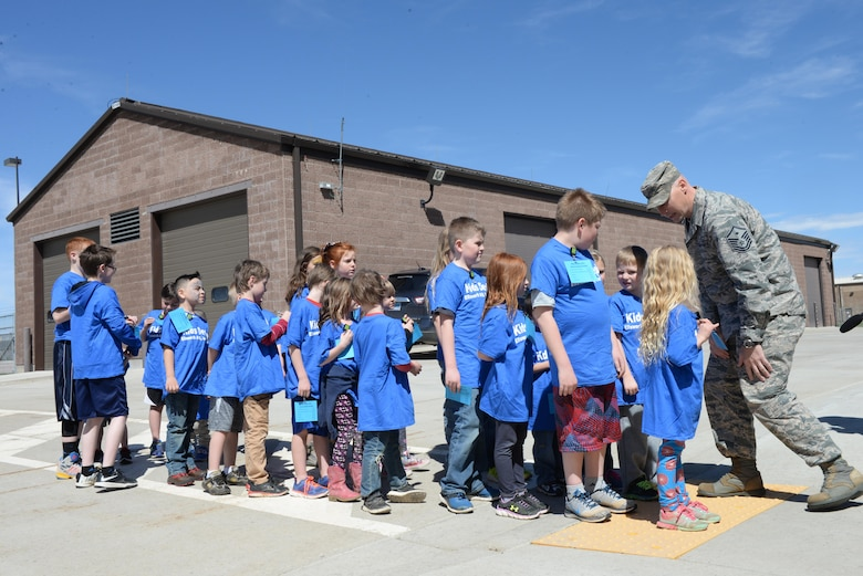 Master Sgt. Jason Cast, the first sergeant assigned to the 28th Security Forces Squadron, places children into a formation before they enter the deployment center on Ellsworth Air Force Base, S.D., April 8, 2017. Cast marched the groups of children participating in the Kid's Deployment Line to and from the deployment center to simulate being deployed.  (U.S. Air Force photo by Airman Nicolas Z. Erwin)