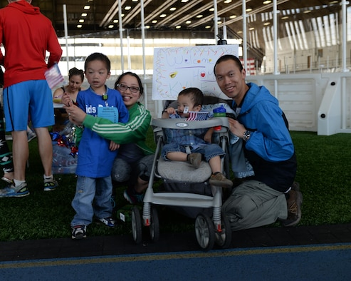 Tech. Sgt. Huy Nguyen, right, a senior weapons system controller assigned to the 28th Maintenance Group, and his family welcome his son back from the deployment center during the Kid's Deployment Line event at Ellsworth Air Force Base, S.D., April 8, 2017. This is the first time the Nguyens have participated in this event with their oldest son, Kyle. (U.S. Air Force photo by Airman Nicolas Z. Erwin)