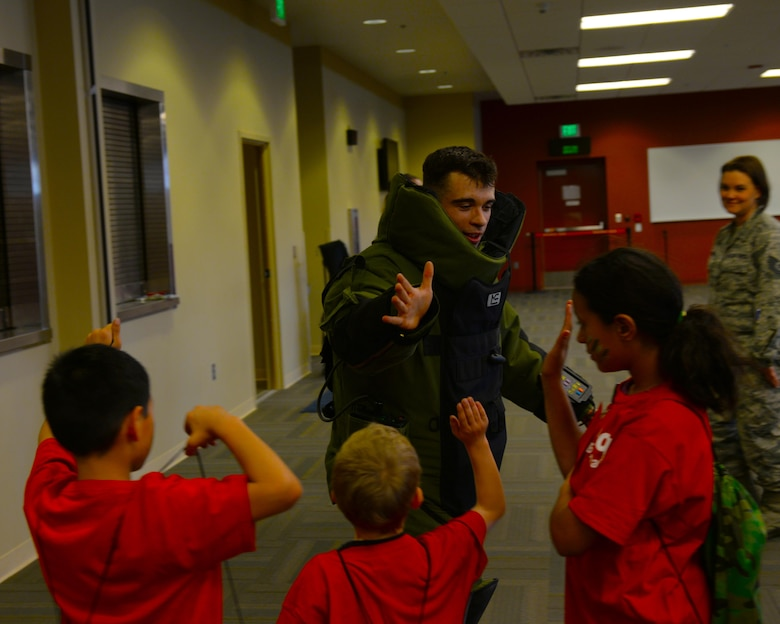 Airman 1st Class George Green, an explosive ordinance disposal technician assigned to the 28th Civil Engineer Squadron, congratulates children participating in the Kid's Deployment Line at the deployment center at Ellsworth Air Force Base, S.D., April 8, 2017. The Kids Deployment Line was a part of the Month of the Military Child, and was planned by the Airman and Family Readiness Center and the Youth Center. (U.S. Air Force photo by Airman Nicolas Z. Erwin)