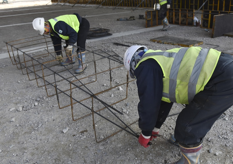 Ko Sung-Soo and Kang Ki-Ok, Republic of Korea contractors, set pieces of rebar into groups at Kunsan Air Base Republic of Korea, March 21, 2017. The rebar will be used to provide structural integrity for the new flow-through shelters being built for the 35th Fighter Squadron at Kunsan. (U.S. Air Force photo by Senior Airman Michael Hunsaker/Released)