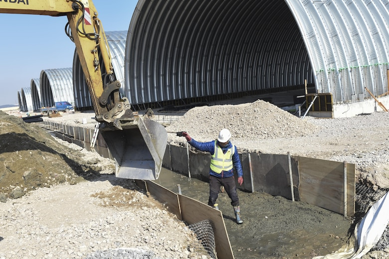 Mun Sung-Hwan, Republic of Korea contractor, guides an excavator bucket into a trench at Kunsan Air Base, Republic of Korea, March 21, 2017. Local contractors were brought to Kunsan to build new aircraft flow-through shelters. These shelters provide a protected area for aircraft to receive fuel and maintenance as quickly as possible during operations. (U.S. Air Force photo by Senior Airman Michael Hunsaker/Released)