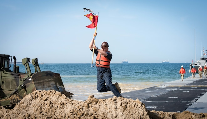 POHANG, Republic of Korea (April 7, 2017) – Spc. Joshua Garcia, attached to 331st Transportation Company, plants the command's flag into the beach after successfully landing the Trident Pier during Operation Pacific Reach Exercise 2017 (OPRex17). OPRex17 is a bilateral training event designed to ensure readiness and sustain the ROK-U.S. Alliance by exercising an Area Distribution Center (ADC), an Air Terminal Supply Point (ATSP), Combined Joint Logistics Over-the-Shore (CLOTS), and the use of rail, inland waterways, and coastal lift operations to validate the operational reach concept. (U.S. Navy photo by Mass Communication Specialist 2nd Class Eric Chan /Released)