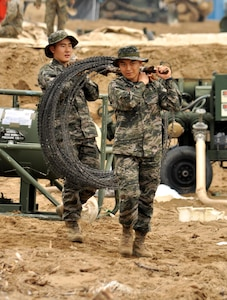 Two members of the Republic of Korea Marine Corps carry a roll of concertina wire across Dogu Beach near the South Korean port city of Pohang, April 6, 2017, as they help prepare for Operation Pacific Reach Exercise 2017. The exercise, also known as OPRex17, is a bilateral training event designed to ensure readiness and sustain the capabilities which strengthen the ROK-U.S. alliance. (Combined Forces Command photo by Sgt. 1st Class John Queen/released)