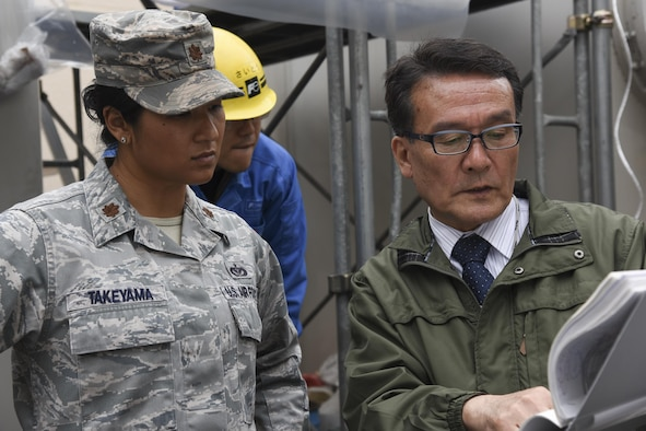 A contractor member from Sanwa Engineering Company, Limited explains the progress of the project to Major Korinne Takeyama, 374th Civil Engineer Squadron operations flight commander, at Yokota Air Base, Japan, April 8, 2017. The 374th Civil Engineer Squadron along with contractors repaired the gas leak from one of the gas-insulated high-voltage switchgear in the West Substation to prevent further damage. (U.S. Air Force photo by Machiko Arita)
