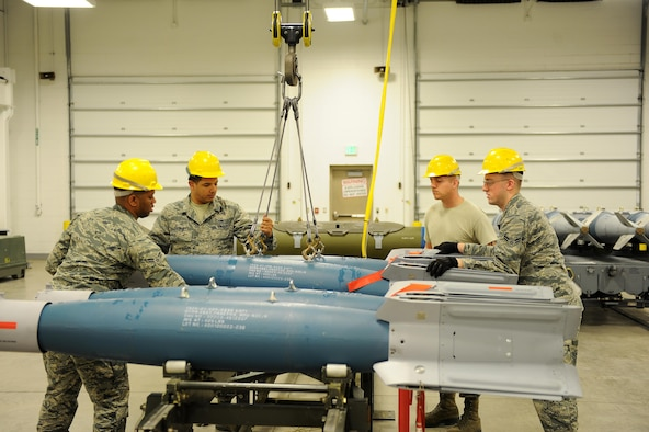 Crew members with the 5th Munitions Squadron conventional maintenance use an indoor crane to move inert GBU-12 bombs onto a rack for maintenance at Minot Air Force Base, N.D., April 5, 2017. Conventional maintenance crew members conduct familiarization and characteristic training to meet armor load standardizations. (U.S. Air Force photo/Senior Airman Kristoffer Kaubisch)