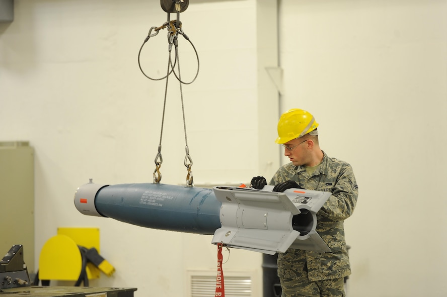 Airman 1st Class Stephen Walters, 5th Munitions Squadron conventional maintenance technician, guides an inert GBU-12 Bomb as it's moved for maintenance at Minot Air Force Base, N.D., April 5, 2017. Situational awareness and teamwork is crucial for safe and effective transport of weapons systems on base. (U.S. Air Force photo/Senior Airman Kristoffer Kaubisch)