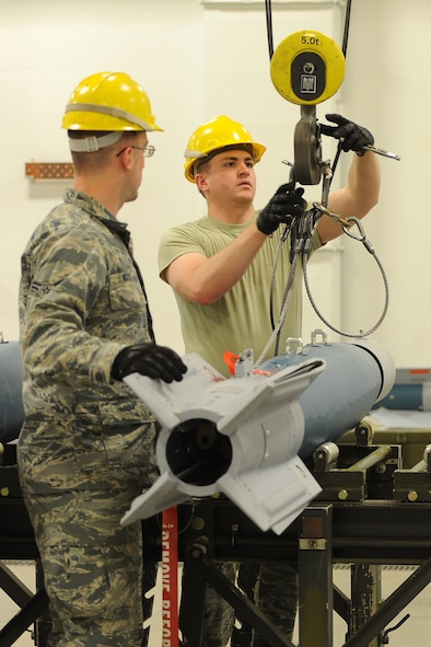 (From left) Airman 1st Class Stephen Walters and Derek Merkley, 5th Munitions Squadron conventional maintenance technicians, unhook an inert GBU-12 bomb from an indoor crane at Minot Air Force Base, N.D., April 5, 2017. Conventional maintenance crew members conduct familiarization and characteristic training to meet armor load standardizations. (U.S. Air Force photo/Senior Airman Kristoffer Kaubisch)