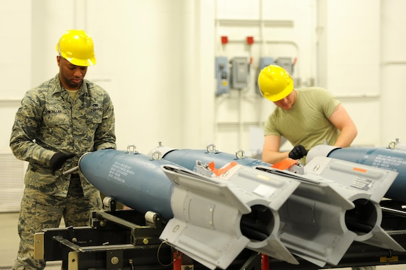 (From left) Airman 1st Class Brandon McMillan and Derek Merkley, 5th Munitions Squadron conventional maintenance technicians, replace the spanner bolt assemblies on inert GBU-12 bombs at Minot Air Force Base, N.D., April 5, 2017. Situational awareness and teamwork is crucial for safe and effective transport of weapons systems on base. (U.S. Air Force photo/Senior Airman Kristoffer Kaubisch)