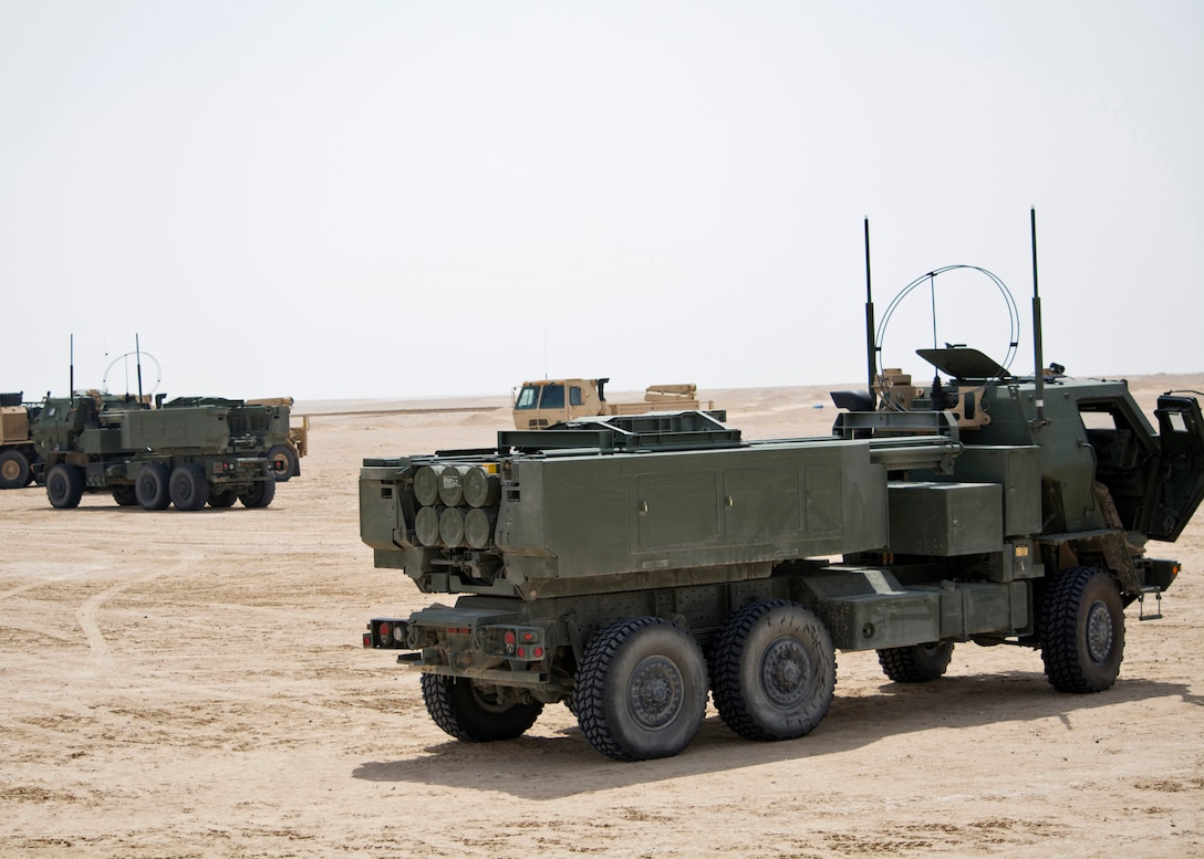 Two High Mobility Artillery Rocket System weapons systems (green), with 3rd Battalion, 157th Field Artillery Regiment, wait at observation point 10 during a live-fire table VI gunnery, March 29, Udairi Range Complex, Kuwait. The purpose of the live-fire gunnery is to validate and qualify the three-man teams required to operate a HIMARS. (U.S. photo by Sgt. Kimberly Browne, USARCENT Public Affairs.)