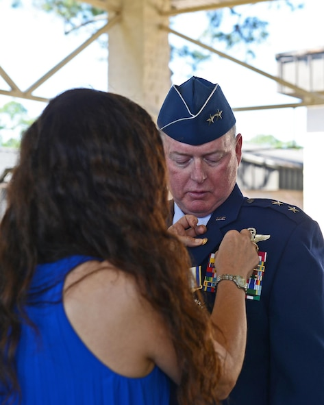 Sally Haase places a retirement pin on Maj. Gen. Eugene Haase's lapel during his retirement ceremony at Hurlburt Field, Fla., April 10, 2017. Haase, the vice commander of AFSOC, acquired more than 3,500 hours as a command pilot. (U.S. Air Force photo/Staff Sgt. Melanie Holochwost)