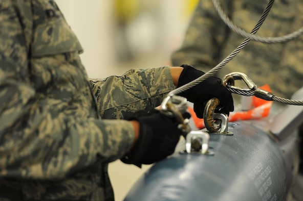 Airman 1st Class Brandon McMillan, 5th Munitions Squadron conventional maintenance technician, unhooks an inert GBU-12 bomb from an indoor crane and loads it onto a flatbed truck at Minot Air Force Base, N.D., April 5, 2017. Conventional maintenance crew members conduct familiarization and characteristic training to meet armor load standardizations. (U.S. Air Force photo/Senior Airman Kristoffer Kaubisch)