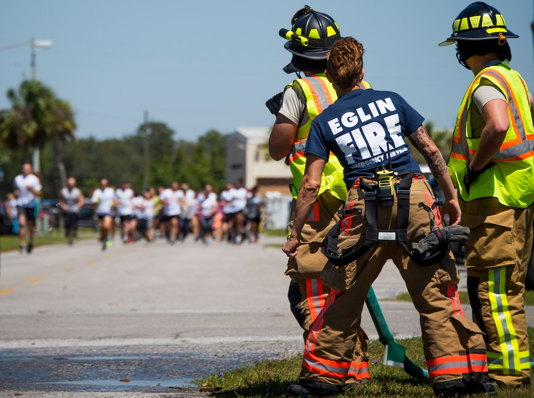 Firefighters prepare to soak participants with water during the 4th annual Color Me Aware Fun Run April 6 near the Civil Engineer Pavilion at Eglin Air Force Base, Fla. The run is held to raise sexual assault awareness. (U.S. Air Force photo/Ilka Cole)