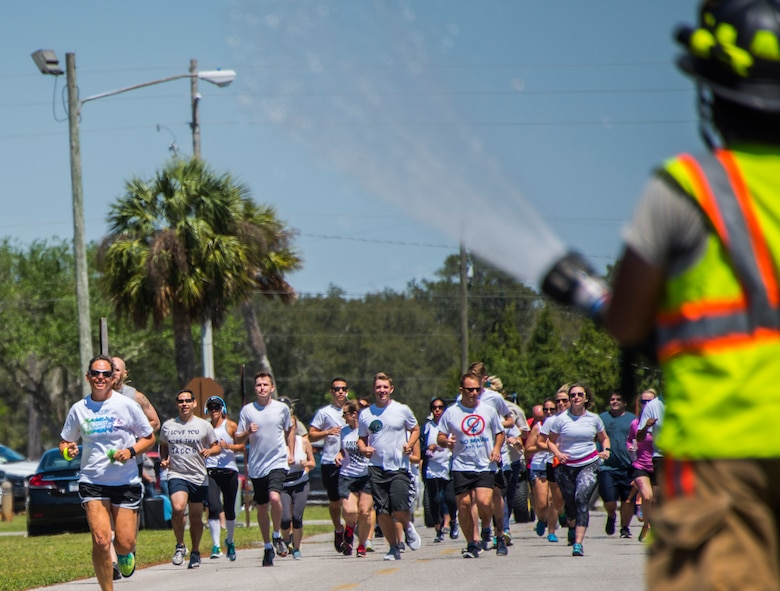 A firefighter sprays water on run participants during the 4th annual Color Me Aware Fun Run April 6 near the Civil Engineer Pavilion at Eglin Air Force Base, Fla. The run is held to raise sexual assault awareness. (U.S. Air Force photo/Ilka Cole)