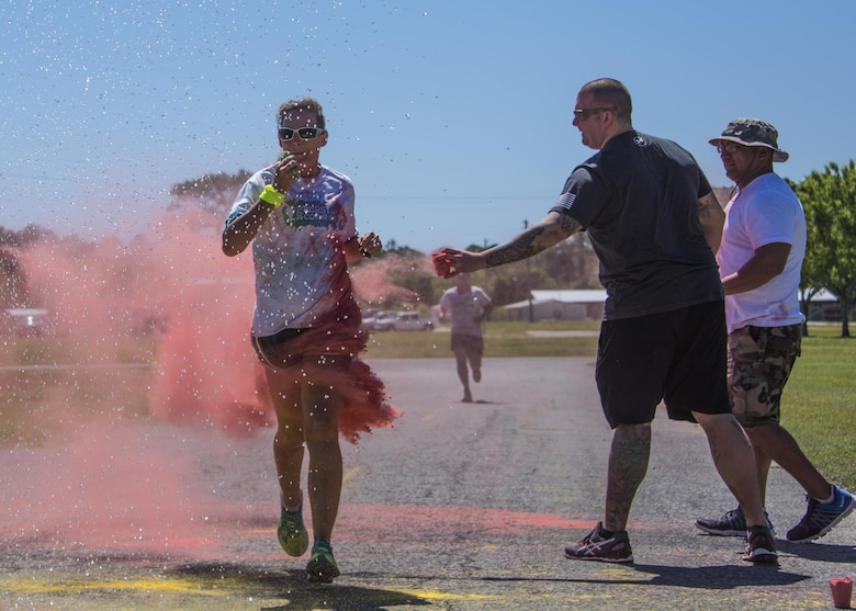 Race volunteers toss colored powder on a runner as she runs through water spray during the 4th annual Color Me Aware Fun Run April 6 near the Civil Engineer Pavilion at Eglin Air Force Base, Fla. The run is held to raise sexual assault awareness. (U.S. Air Force photo/Ilka Cole)