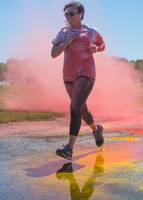 A runner moves through a pink cloud of powder toward the finish line during the 4th annual Color Me Aware Fun Run April 6 near the Civil Engineer Pavilion at Eglin Air Force Base, Fla. The run is held to raise sexual assault awareness. (U.S. Air Force photo/Ilka Cole)