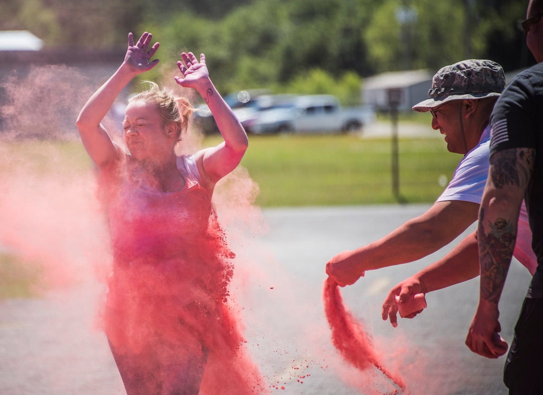 A runner squints through a pink cloud of powder during the 4th annual Color Me Aware Fun Run April 6 near the Civil Engineer Pavilion at Eglin Air Force Base, Fla. The run is held to raise sexual assault awareness. (U.S. Air Force photo/Ilka Cole)