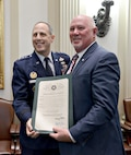 Rep. Roger Ford, R-Midwest City, presents Lt. Gen. Lee K. Levy II, Air Force Sustainment Center Commander, with a proclamation honoring Tinker's 75th Anniversary. (Air Force photo by Kelly White)