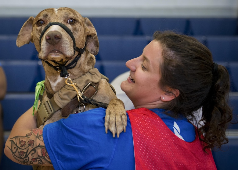 Retired Senior Airman Hannah Stolberg, and her service dog, Valhalla, share a moment during the adaptive sports camp at Eglin Air Force Base, Fla., April 2016.  The base will hosts the week-long Warrior CARE event again this year, helping recovering wounded, ill and injured military members through specific hands-on rehabilitative training.  (U.S. Air Force photo/Samuel King Jr.)