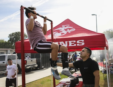 Cpl. Mario Miranda (Right) counts pull-ups for a high school wrestler at the Frankie Ramos JV Wrestling Tournament at Imperial High School, Imperial, Calif. on Jan. 7, 2017, The tournament was started six years ago to honor Frankie Ramos and celebrate his life as a successful wrestler and Marine. Ramos passed away while serving as a recruiting aid in Imperial on March 19, 2010. Miranda, from Imperial, Calif. is a warehouse clerk with Headquarters and Service Company, 4th Tank Battalion, 4th Marine Division. (U.S. Marine Corps photo by Sgt. William Hester/ Released)