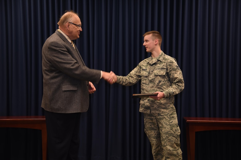 Sioux Falls, S.D. - Staff Sgt. Zac Hakinson, 114th Communication Flight information technology specialist, receives his collage diploma from Dr. Richard Hanson, Dakota State University Provost and Vice President for Academic Affairs, April 11, 2017, Joe Foss Field, S.D. Hakinson received his diploma prior to deploying for a Reserve Component Period. (U.S. Air National Guard photo by Staff Sgt. Duane Duimstra/Released)