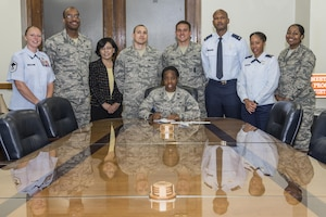 Lt. Col. Tamona Bright, 502nd Security Readiness Group staff judge advocate, signs her Air Force Assistance Fund pledge with Joint Base San Antonio AFAF installation project officers, unit project officers and key workers April 10, 2017, at Joint Base San Antonio-Randolph. The AFAF campaign, made up of Air Force Villages Inc., Air Force Aid Society Inc., Air Force Enlisted Village Inc. and the General and Mrs. Curtis E. LeMay Foundation, help eligible recipients with emergencies, educational support or securing retirement homes for widows or widowers of Air Force members in need of financial assistance. (U.S. Air Force photo by Senior Airman Stormy Archer)