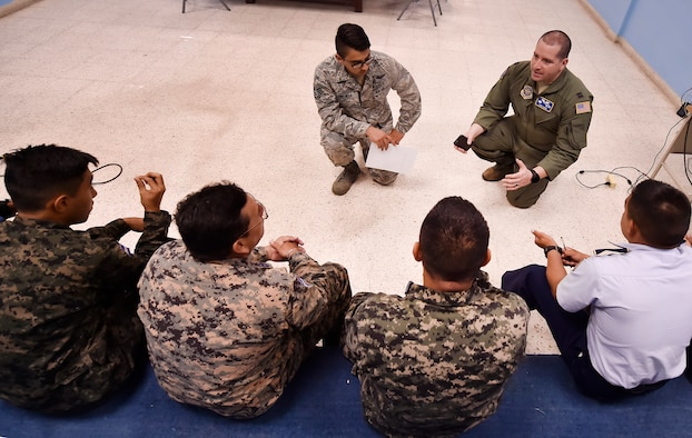 U.S. Air Force Staff Sgt. Gabriel Trujillo, 779th Medical Operations Squadron paramedic, Joint Base Andrews, Maryland, top left, and U.S. Air Force Capt. Diego Torres, Detachment 4, 375th Operations Group flight nurse instructor and evaluator, Wright-Patterson Air Force Base, Ohio, top right, talk about aerospace medicine best practices during a round table discussion as part of a subject matter expert knowledge exchange in Tegucigalpa, Honduras, April 5. The global health engagement brought U.S. and Honduran counterparts together to build and strengthen partner relationships.