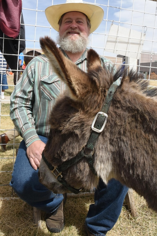 Nathan Lincoln, Noah's Ark Petting Zoo and Pony Ride owner, supervises the petting zoo area during the annual Spring Fling event at Schriever Air Force Base, Colorado, Saturday, April 8, 2017.  One of his mules, Gus, stares at Lincoln begging for treats in between children's pets.  (U.S. Air Force photo/Tech. Sgt. Sara Bishop)