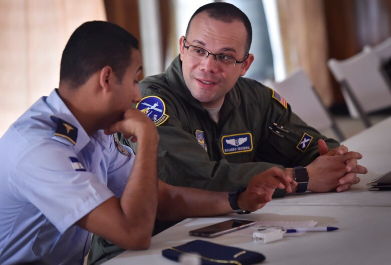 U.S. Air Force Capt. Ricardo Sequeira, 628th Medical Operations Support Squadron and 14th Airlift Squadron flight surgeon, Joint Base Charleston, South Carolina, right, talks to a member of the Honduran air force about flight medicine during an aerospace medicine subject matter expert exchange in Tegucigalpa, Honduras, April 4. The goal of the global health exchange is to share best practices, enhance relationships, and build partnership capacities.