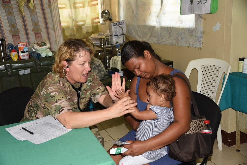 Sgt. 1st Class Loraine Branson, Joint Task Force-Bravo's Medical Element, high fives a local Nicaraguan child during the screening process at Medical Readiness Exercise in the village of Waspam March 30. Personnel from the Joint Task Force-Bravo Medical Element worked side by side with local nurses and physicians, as well as Nicaraguan soldiers to provide the population with immunizations, preventive medicine, dental services, basic medical care and pharmacy services during the three day exercise.