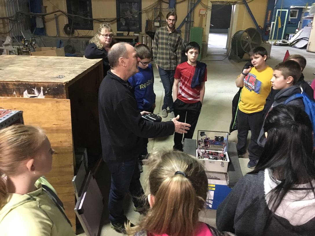 Blue Mountain Union School students recently visited the U.S. Army Engineer Research and Development Center's Cold Regions Research and Engineering Laboratory as part of an education outreach program effort. Research Civil Engineer Leonard Zabilansky works throughout the year with the students in the classroom; the student's CRREL visit helps solidify the classroom instruction. In the photo, CRREL Researcher Dr. Jim Lever talks with the students about the robots he has designed, built and deployed in both the Arctic and Antarctic.