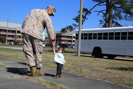 MARINE CORPS AIR STATION CHERRY POINT, N.C.—Cpl. Joseph Capellini walks with his daughter while his family waits to bid him farewell for a deployment from Marine Corps Air Station Cherry Point, N.C., March 29, 2017. The mission of Marine Tactical Electronic Warfare Squadron 3, Marine Aircraft Group 14, 2nd Marine Aircraft Wing, during the deployment will be to conduct airborne electronic warfare in support of operations. This includes the EA-6B Prowler's unique ability to suppress enemy radar and surface-to-air missiles utilizing electronic jamming and high-speed anti-radiation missiles, as well as collect tactical intelligence in a passive electronic support role. Capellini is a hydraulic mechanic with Marine Aviation Logistics Squadron 14, MAG-14, 2nd MAW. (U.S. Marine Corps photo by Cpl. Mackenzie Gibson/ Released)