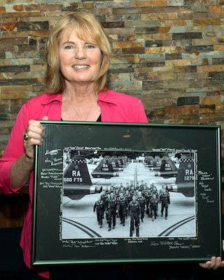 Christina Olds, daughter of retired Brig. Gen. Robin Olds, holds a photograph presented to her by the 560th Flying Training Squadron at the Auger Inn on Joint Base San Antonio-Randolph, Texas, March 30, 2017. Olds shared stories of her father's distinguished Air Force career as a triple ace. (U.S. Air Force photo by Staff Sgt. Michelle Patten)