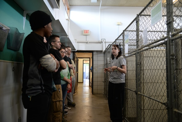 Alexis Topham, Souris Valley Animal shelter kennel assistant, speaks with 5th Logistics Readiness Squadron Airmen at the animal shelter in Minot, N.D., March 29, 2017.  The 5th LRS volunteers walked and played with the dogs during their visit to the shelter. (U.S. Air Force photo/Airman 1st Class Dillon J. Audit)