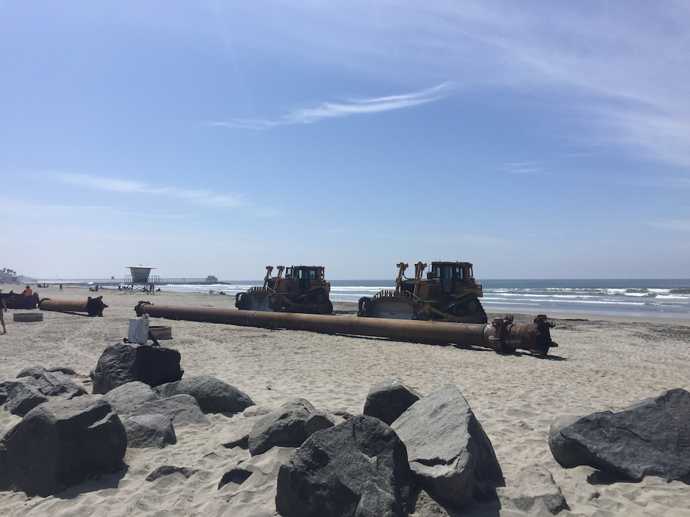 Tractors and pipe are pre-positioned at Oceanside Beach in preparation for the Oceanside Harbor navigation dredging project. The pipe will transport beach quality sand from the harbor entrance channel to renourish the beach south of the San Luis Rey River.