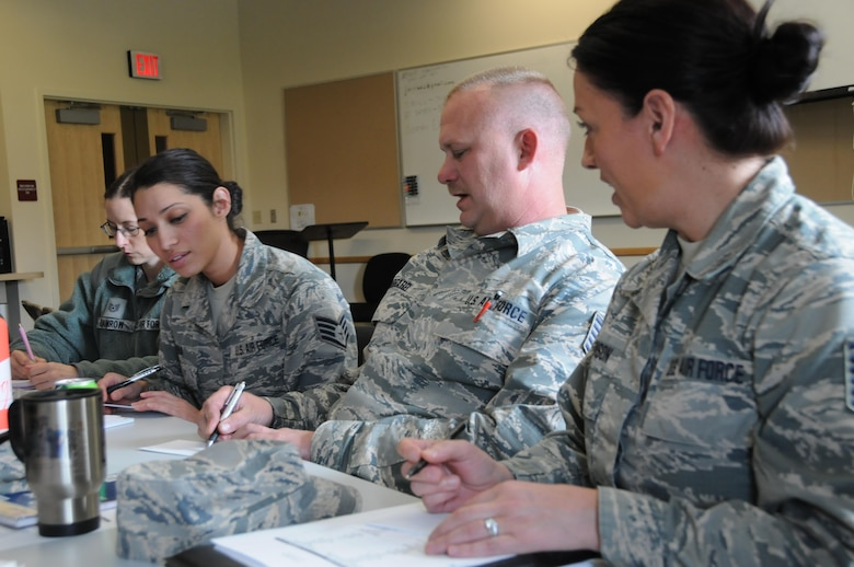 During an exercise demonstrating lean principles, from right, Master Sgt. Melissa Monson, Tech. Sgt. James Hubbard and Staff Sgt. Dianna Pena and Tech. Sgt. Shawna Damrow work as a team to prepare identical sets of index cards in as short a time as possible. The 8-Steps to Problem Solving class stresses process analysis as a way to identify waste and increase efficiency. (U.S. Air National Guard photo by Tech. Sgt. Jefferson Thompson)