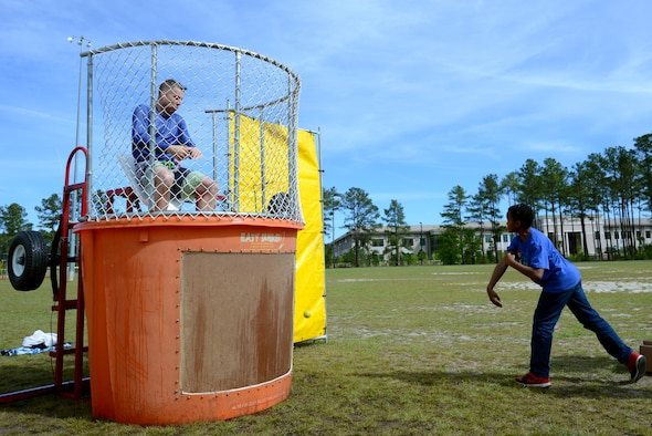 U.S. Air Force Lt. Col. William Clayton, 20th Force Support Squadron commander, left, falls into a tank of water after a Team Shaw child hits a target with a ball during a Month of the Military Child (MOMC) celebration at Shaw Air Force Base, S.C., April 8, 2017. The MOMC was first recognized in 1986 to show support for military children and highlight the sacrifices they make while their parents serve. (U.S. Air Force photo by Airman 1st Class Kathryn R.C. Reaves)
