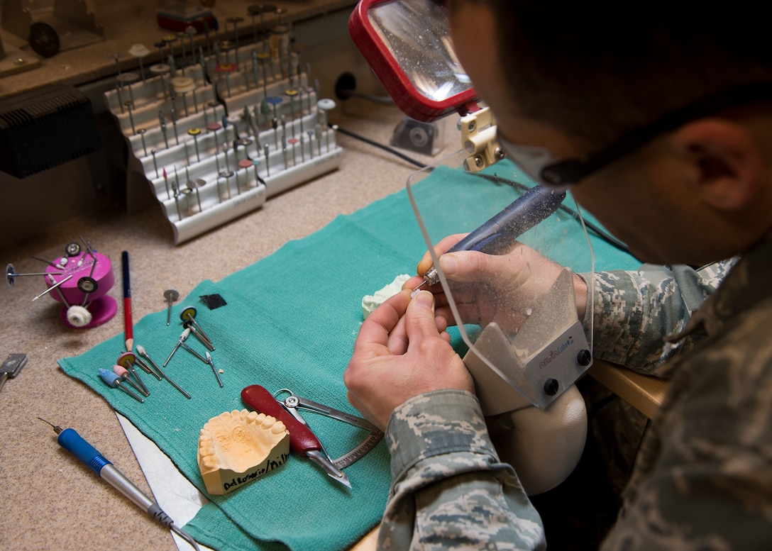 Tech. Sgt. Manuel Painter, 92nd Aerospace Medicine Squadron dental technician, mills down a cast tooth as part of the crown making process April 07, 2017, at Fairchild Air Force Base, Wash. Crown making is an intensive process that requires a series of casting, milling and coating steps. (U.S. Air Force photo/A1C Ryan Lackey)