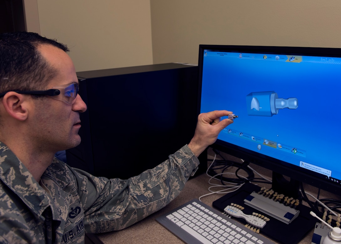 Tech. Sgt. Manuel Painter, 92nd Aerospace Medicine Squadron dental technician, displays a milling block and its computer simulated 3-D model prior to milling April 07, 2017, at Fairchild Air Force Base, Wash. New advances in dental machining has enabled technicians to recreate teeth with greater speed and precision. (U.S. Air Force photo/A1C Ryan Lackey)