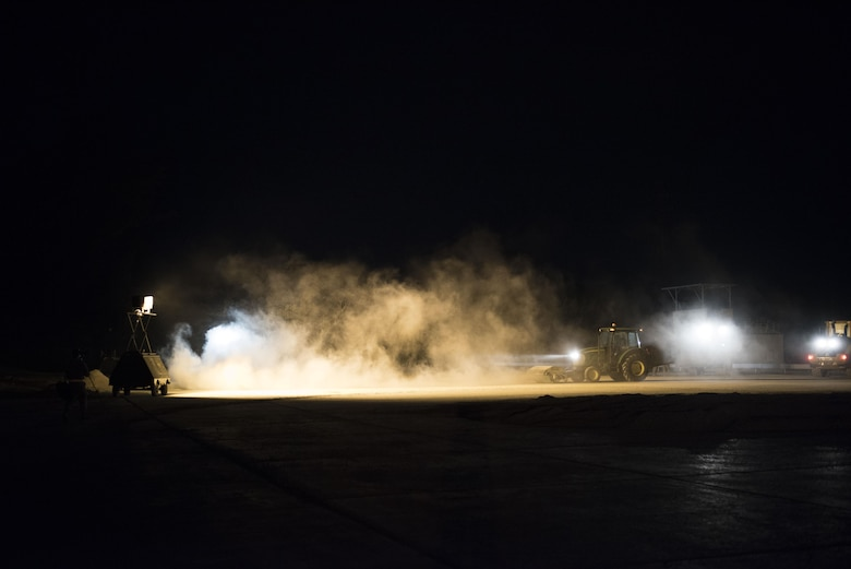U.S. Air Force civil engineer Airmen use specialized equipment to clear debris from a runway during a no-notice exercise April 12, 2017, at Kadena Air Base, Japan. During the airfield damage repair portion of the exercise, the 18th CES trains throughout the night to ensure mission capability in all conditions. (U.S. Air Force photo by Senior Airman Omari Bernard/Released)