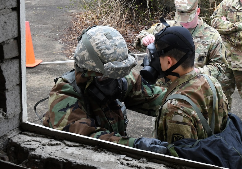 U.S. Army Pfc. Sung Hoon Lee, 2nd Battalion, 1st Air Defense Artillery medic, simulates decontaminating a Soldier during the 35th Air Defense Artillery Brigade Expert Field Medical Badge preliminary competition at Osan Air Base, Republic of Korea, April 6, 2017. During the competition, participants had to overcome two combat trauma lanes, testing the medic's abilities, determination and strength through scenarios such as medical management, care under fire, tactical movement, decontamination and litter movement. (U.S. Air Force photo by Staff Sgt. Alex Fox Echols III)