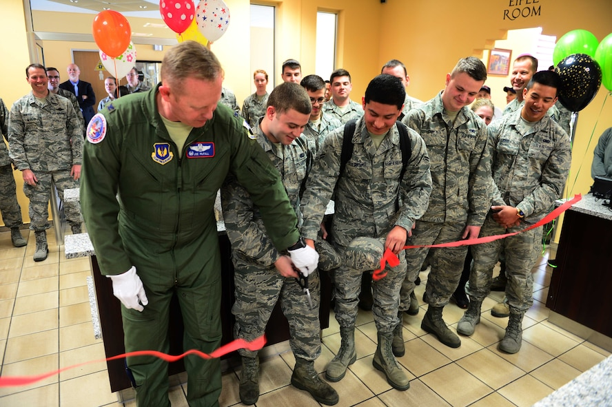 Col. Joseph McFall, 52nd Fighter Wing commander, and Spangdahlem Airmen cut the ceremonial ribbon at the updated Dining Facility at Spangdahlem Air Base after several months of renovations that made meal service unavailable to the Saber community, April 10, 2017. Upgrades to the DFAC include new kitchen equipment like ovens and a walk in fridge, air conditioning installed in the kitchen, a new service line, repainting the walls and adding murals in the dining rooms to reflect the base's connection to the local community. (U.S. Air Force photo by Senior Airman Joshua R. M. Dewberry)