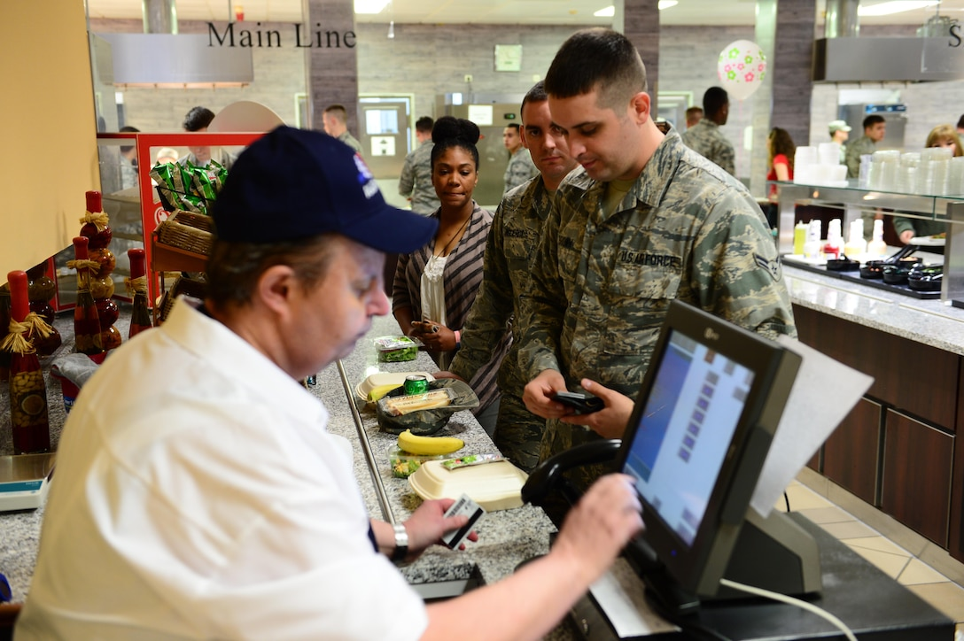 Airmen pay for their first lunch at the updated Dining Facility at Spangdahlem Air Base after several months of renovations that made meal service unavailable to the Saber community, April 10, 2017. Upgrades to the DFAC include new kitchen equipment like ovens and a walk in fridge, air conditioning installed in the kitchen, a new service line, repainting the walls and adding murals in the dining rooms to reflect the base's connection to the local community. (U.S. Air Force photo by Senior Airman Joshua R. M. Dewberry)