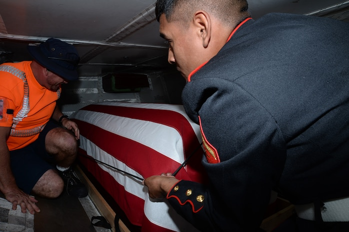 Lance Cpl. Tomas Nolasco Jr.,  Marine Corps Logistics Base Albany funeral detail member, drapes an American flag over a casket with the remains of Marine Pfc. James O. Whitehurst at the Tallahassee International Airport in Tallahassee, Fla., April 11. Whitehurst was killed in action at the battle of Tarawa during World War II, Nov. 20, 1943.