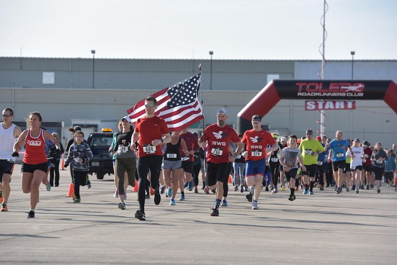 Runners take off from the start line at the I Believe I Can Fly 5k race at the Toledo Express Airport in Swanton, Ohio on April 9, 2017. The 180th Fighter Wing's Company Grade Officer Council partnered with the non-profit organization, The Arms Forces, as well as local law enforcement, fire departments and civilian volunteers to hold the third annual race which had approximately 270 participants, to raise awareness for military members with post-traumatic stress disorder and traumatic brain injury. The race, now in its third year, provides runners of all ages, the rare opportunity to run a unique course, down the taxiways used by Northwest Ohio's very own 180FW, while also promoting awareness and raising funds to benefit our veterans who have given so much to our great nation. (U.S. Air National Guard photo by Tech. Sgt. Nic Kuetemeyer)